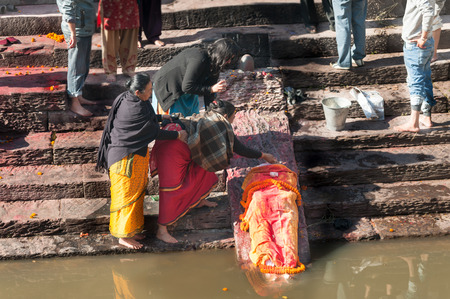 cremated: KATHMANDU, NEPAL - DECEMBER 19, 2012: Nepali local people during the cremation ceremony along the holy Bagmati River in Bhasmeshvar Ghat at Pashupatinath temple. The importance of Bagmati also lies in the fact that Hindus are cremated on the banks of this
