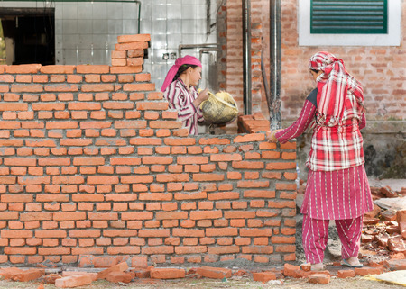KATHMANDU, NEPAL - DECEMBER 17, 2012: Nepali construction mason women workers bricklayer making a brickwork with trowel and cement mortar. The economic contribution of women was substantial, but largely unnoticed because their traditional role was taken f