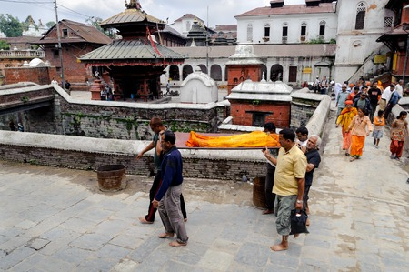 cremated: KATHMANDU, NEPAL - JULY 2, 2013: Nepali local people carrying a dead body to the cremation ceremony along the holy Bagmati River in Bhasmeshvar Ghat at Pashupatinath temple.The importance of Bagmati also lies in the fact that Hindus are cremated on the ba