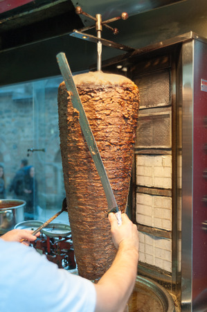 Doner kebab Turkish d?ner is being cut before serving by chef at restaurant in istanbul Imagens