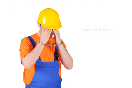 blue collar: failure guilty laborer regretful criminal handcuffed hard hat blue collar portrait on wihte background Stock Photo