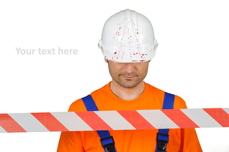 injured laborer at accident scene hard hat with blood and warning tape on white background Stock Photo