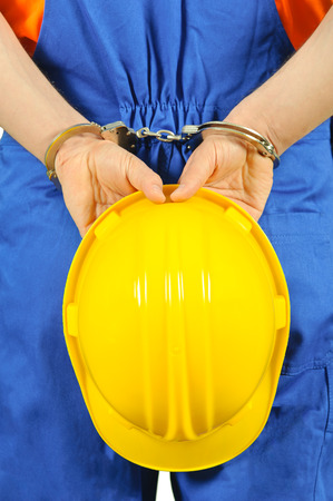 failure guilty laborer regretful criminal handcuffed hard hat blue collar portrait on white background