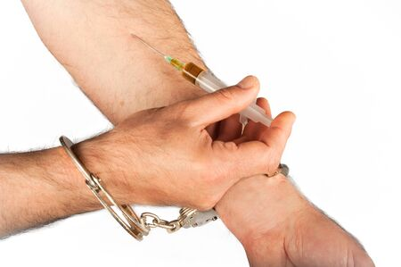 self harm: handcuffed hype applying injection shot in hand Isolated on white background