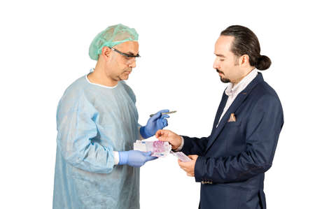 doctor money: businessman paying surgery fee to surgeon isolated on the white background