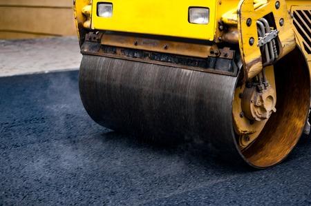 steamroller: Compact steamroller flatten out the asphalt.