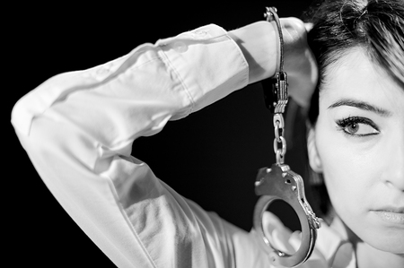 gefesselt: bedauernden Mädchen weißen Kragen in Schwierigkeiten in Handschellen isoliert auf schwarzem Hintergrund Schwarz-Weiß-