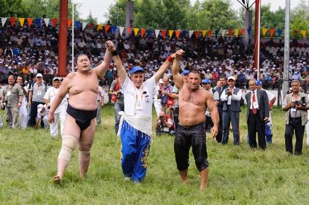 greased: EDIRNE, TURKEY - JULY 26, 2010: Wrestlers Turkish pehlivan and Japanese sumo wrestler at the competition in Kirkpinar. Kirkpinar is a Turkish oil-wrestling (Turkish: yagli gures) tournament.