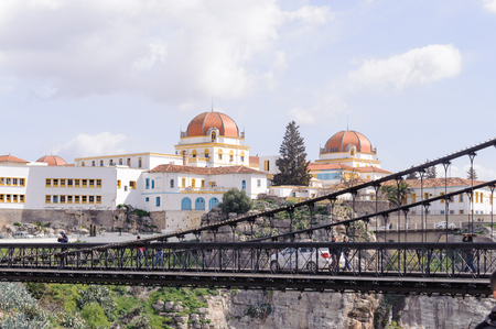 passerby: CONSTANTINE, ALGERIA - MARCH 07, 2017: University Hospital near by the suspension bridge or footbridge of Sidi M Cid crosses the gorges 175 meters above the cliff. Designed by the engineer F. Arnodin.