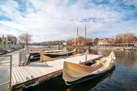 AVANOS, TURKEY - JAN 23, 2019: Nostalgic touristic trip boats near by wooden hanging bridge on snowy winter time in Kizilirmak river touristic Avanos town Nevsehir turkey