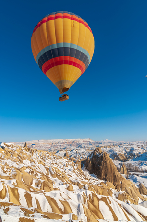colorful balloon over the extraordinary rocks formations rock hills on snowy winter of Cappadocia Nevsehir