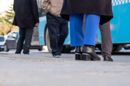 low angle view legs of male and female passengers waiting for bus in bus stop in Istanbul, Turkey with copy space