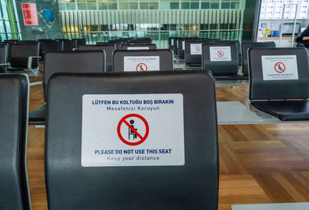 close up of empty chairs with warning to leave empty and seats for passengers in Istanbul airport in quarantine days