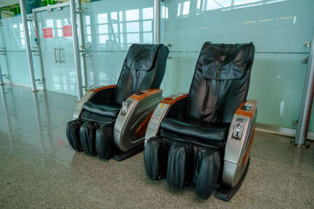 Gaziemir, Izmir, Turkey - 03.11.2021: two empty leather massage chairs in Aydin Menderes Airport for passengers