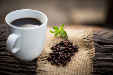 coffeetree: Cup of black coffee and coffee beans on wooden background.