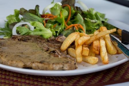 grilled pork chop: juicy grilled pork chop (neck cut) with greens