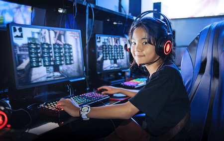 young girl playing game computer online in internet cafe