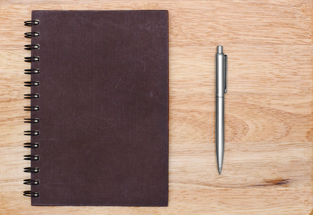 empty cover notebook with pen is on wood background