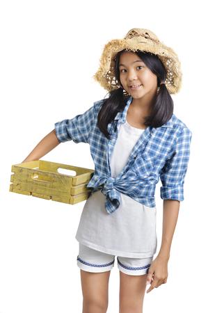 girl farmer holding yellow wooden basket isolate