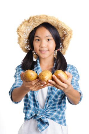 gardener girl carrying fresh potato portrait in studio and focus point at potao