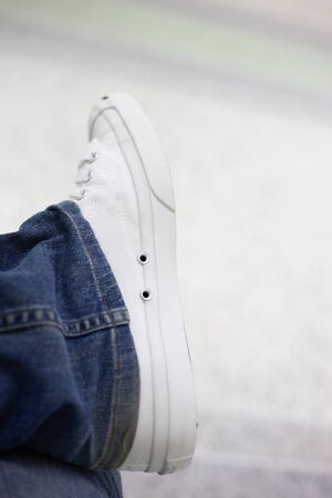 White shoes with jeans sitting at the park.Foot and legs seen from above.Selfie great for any use. 版權商用圖片