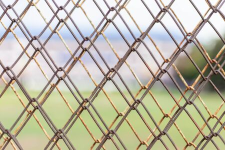 Wire fence with green grass on background.cage background