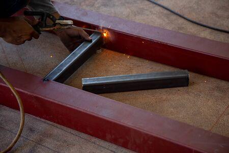 Worker welding steel with sparks using mig mag welder