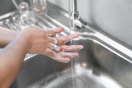 Washing hands man rinsing soap with running water at sink, Coronavirus prevention hand hygiene. Corona Virus pandemic protection by cleaning hands frequently.
