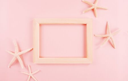 Summer concept with starfishes and photo frame on pink background.