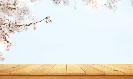 wooden table top with the nature landscape, spring flowers as frame and free space for text
