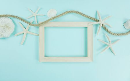 Summer concept with seashells and photo frame on cyan background. Stok Fotoğraf