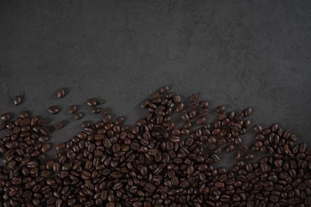 brown roasted coffee beans and coffee cup