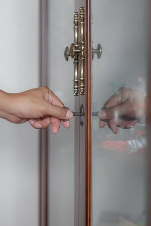 key cabinet: Photo of male hand putting cabinet key into front door lock of cabinet