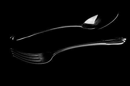 fork and spoon on a black table dark tone