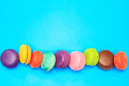 Macaroons put in a row, macaroons on blue background Stock Photo