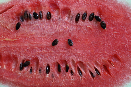 Sweet crimson watermelon, its seeds arranged in a smiling image. Imagens