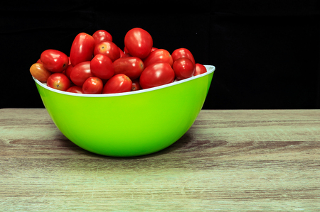 Tomatoes in bowl on black background,wooden Imagens