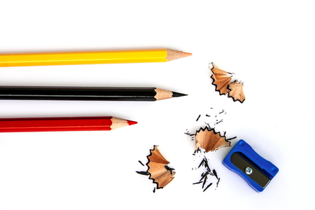 Three pencils are on the white background.They are red , yellow and black color.And on a white background there are pencil sharpener and pencil scraps.