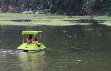 Mother and daughter are driving a pedalo on the lake. Imagens