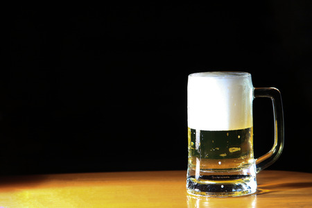 The light from left side of the beer glass. The background is not light, so it is dark and out of focus.