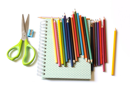 The colored pencils and notebook are on white background.