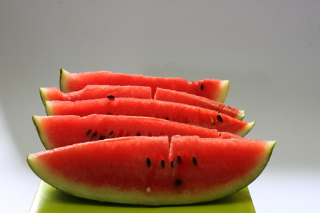 Five sliced red watermelons on green box