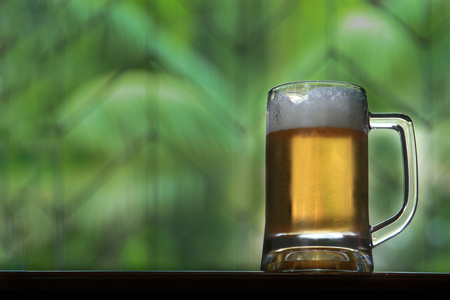 Beer in glass on wooden table with wrought iron and blurry leaves as background. Imagens
