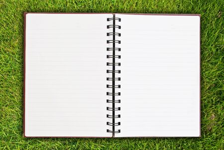 White notebook on grass field texture. photo