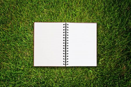 White notebook on grass field texture. photo