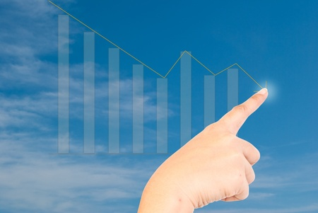 Hand pressing down graph on the blue sky. photo