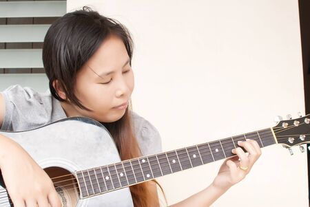 Lady playing classic acoustic guitar. photo