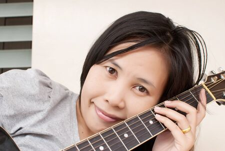 Lady playing classic acoustic guitar. Stock Photo - 10047005