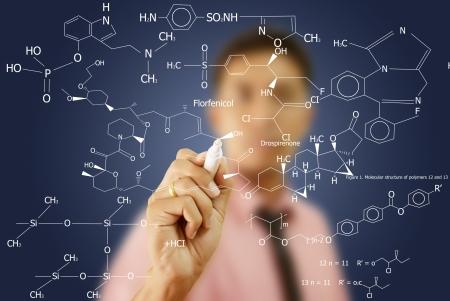 quimica organica: Maestro asi�tico escribir la f�rmula cient�fica en la pizarra. Foto de archivo