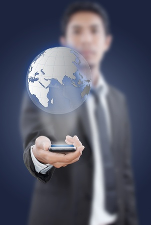 ringtones: Businessman putting touch screen mobile phone with globe. Stock Photo
